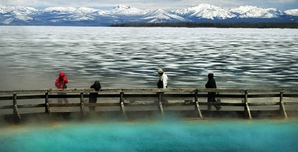 Tourists walk beside a hot spring and the partially frozen Yellowstone Lake at the West Thumb Geyser Basin in the Yellowstone National Park, Wyoming, June 2011.
